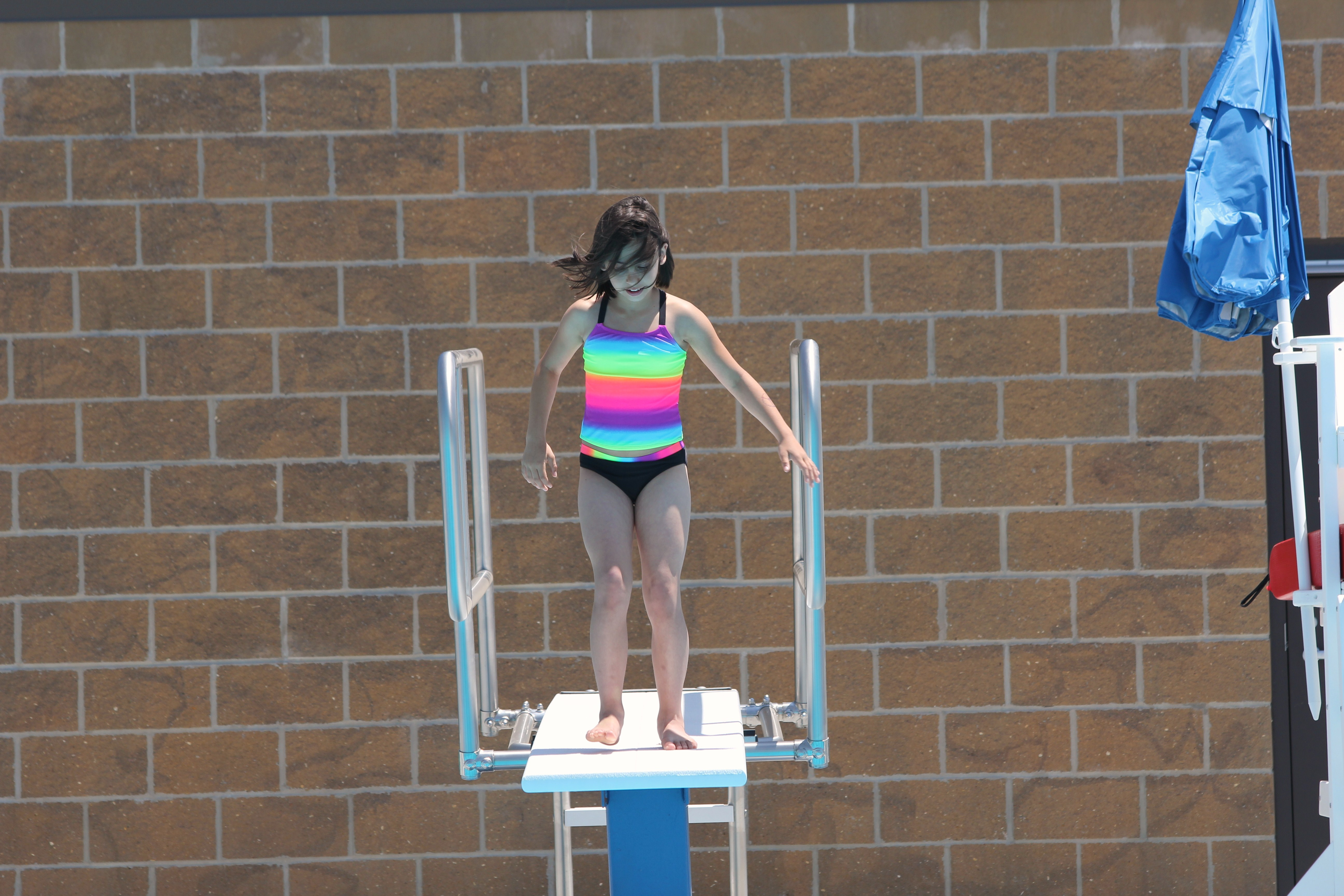 Getting ready to go off the diving board.